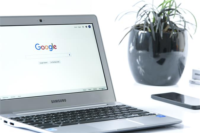 A samsung Chromebook on a desk with a white background, cell phone, and plant