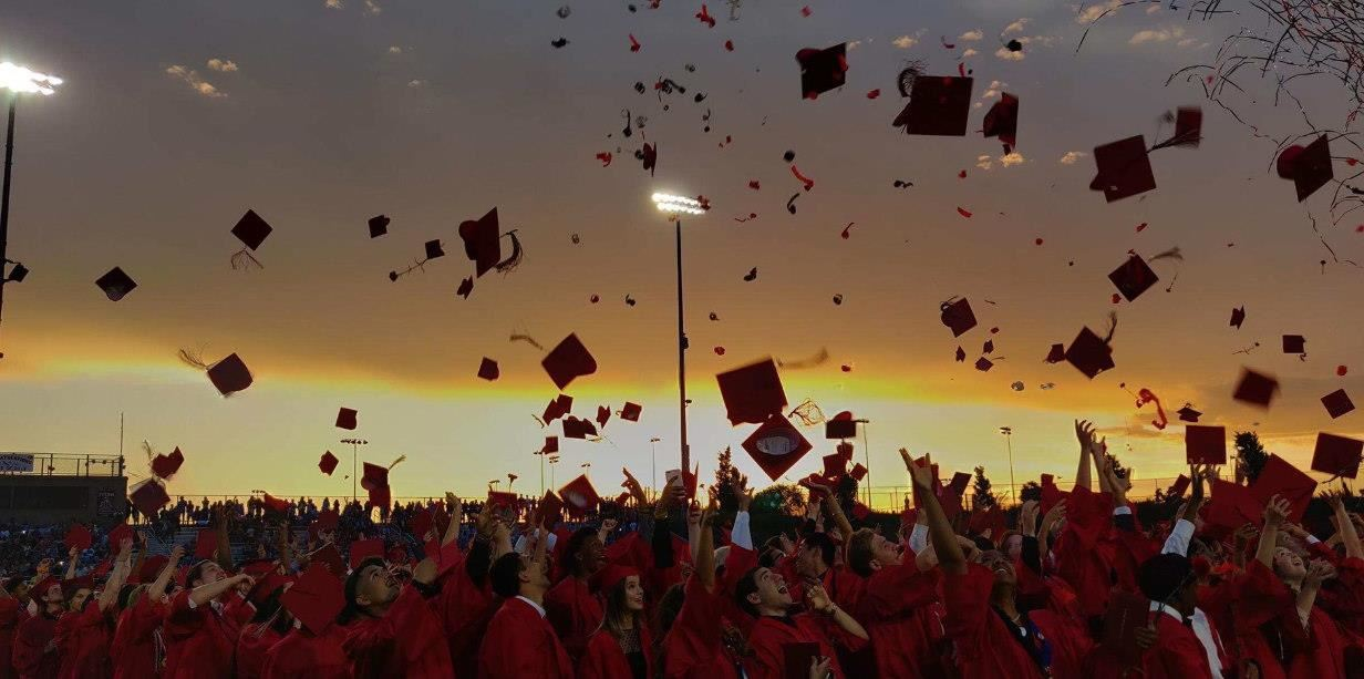 Picture of Antelope High School graduates in red robes throwing their caps in the air, with a sunset in the background.